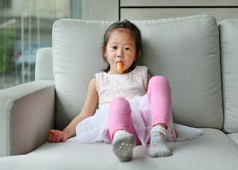 Little girl eating sausage on the sofa.