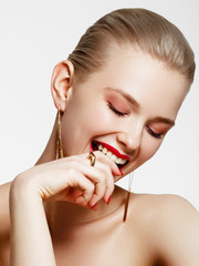 Makeup products. Young beautiful girl with gold earrings and ring smiling on white background. Red nails with manicure and white smile. Young woman with fashion accessories