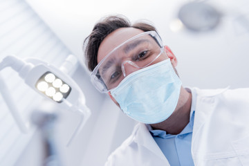 bottom view of dentist in white coat, protective mask and glasses in dental clinic