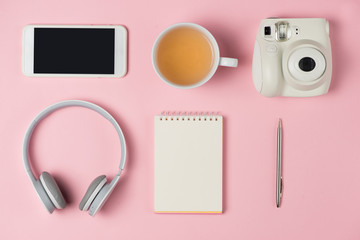 Top view of working desk with blank notebook with pen, tea cup, mobile phone and camera on wooden background