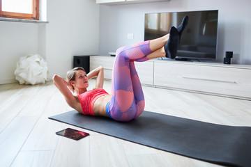 Ragazza con abbigliamento sportivo si allena a casa con tablet