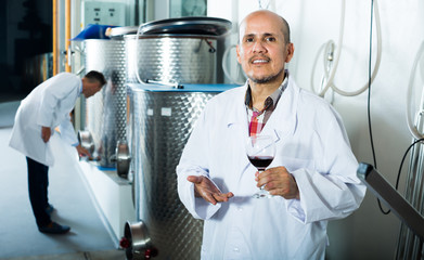 Mature winery worker holding glass of wine