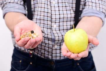 Idea of proper nutrition and treatment. Mans hands hold apple