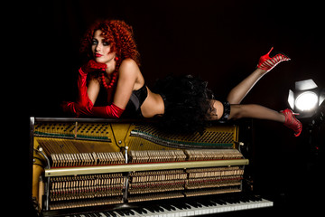 Sexy girl looks like a doll with curly redhead lies on a piano, on a black background. old fashion style