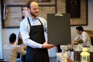 Waiter holding blackboard