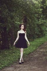 Beautiful young brunette girl in short black dress walking through the woods