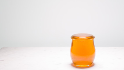 Perfectly full jar of honey with copy space to the left.  Life is full and sweet!