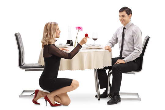 Young woman kneeling and proposing to her boyfriend