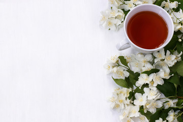 A Cup of black tea with fragrant Jasmine flowers on white background