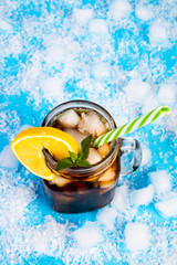 summer drink with ice and lemon on blue background