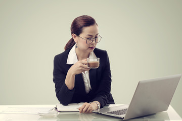 Young businesswoman working in front of laptop and sipping coffee.