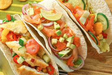 Different tasty fish tacos on wooden background