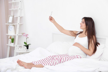 Pregnant woman with mobile phone sitting on bed