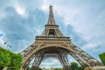 Prospective view of Tour Eiffel, symbol and icon of Paris. Paris Eiffel Tower lower panorama from bottom in Champ de Mars garden, from Paris in France. Europe travel concept.