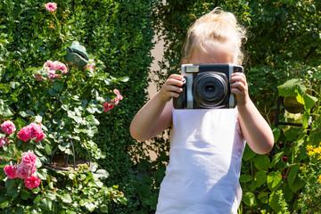 blondes Mädchen fotografiert in die Kamera im Garten