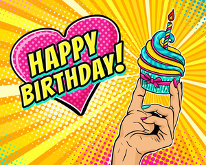 Pop art background with female hand holding cupcake with burning candle and speech bubble in form of heart with Happy Birthday text. Vector illustration in retro comic style. Party invitation poster.
