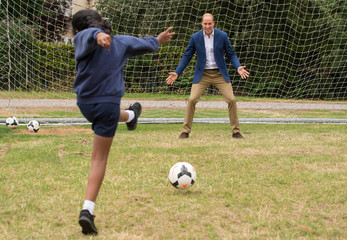 Britain's Prince William joins football practice with children from the Wildcats Girls' football programme, during a reception for the England women's football team, at Kensington Palace in central London