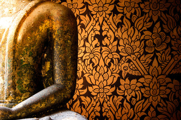 Native Thai Buddha statue and Thai painted style of textured wall in ancient buddhist temple. Thai general line art pattern for background.