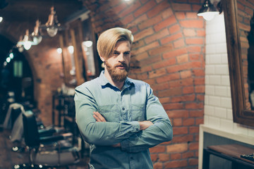 Close up of a stunning look of a red bearded blond guy with trendy hairdo in a barber shop. Looking so fashionable and confident, harsh and severe