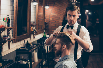Young stylish bearded guy is in a barber shop, getting brend new haircut from a classy dressed stylist. Both are serious and attractive