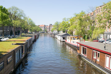 Colorful traditional living houses and houseboats along the canal in Amsterdam, Netherlands