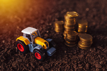 Agricultural tractor toy and golden coins on fertile soil land