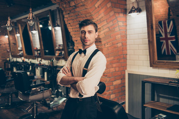 Welcome to barber shop! Attractive young brunette guy with bristle in a barber shop, standing with crossed hands, dressed classy in a retro style. Looking hot and flirty