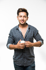 Portrait of a Young handsome Indian man having a cup of coffee, standing isolated over white background