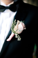 groom's boutonniere of red color hanging on the waistcoat