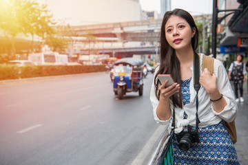 Woman walking in bangkok city using phone app