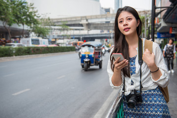 Woman walking in bangkok city using phone