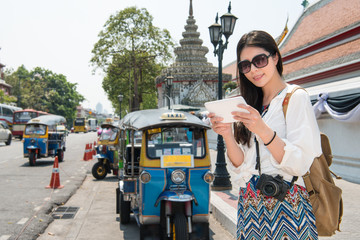 Tablet woman walking near Wat Pho in bangkok.