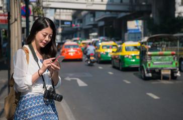 Asian backpacker woman using mobile phone app