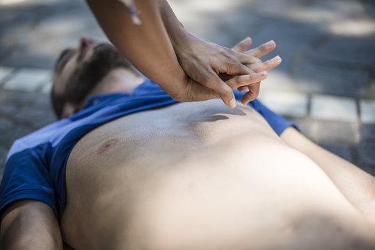 massaggio cardiaco a un ragazzo svenuto a seguito di arresto cardiaco in un parco