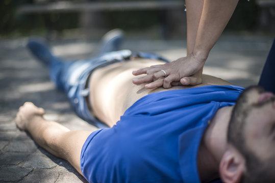 ragazza esegue rianimazione cpr con massaggio cardiaco a giovane svenuto dopo arresto cardiaco