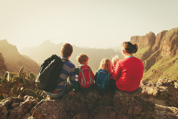 family with three kids hiking in mountains