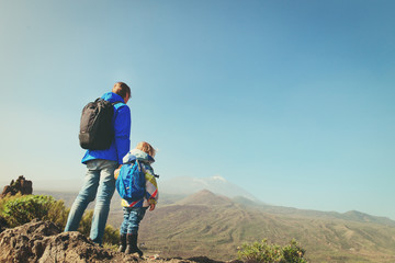 father and little daughter hiking in mountains
