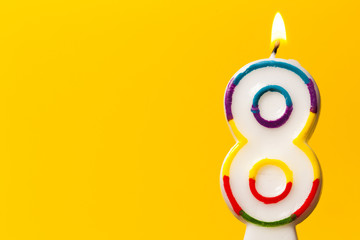 Number 8 birthday celebration candle against a bright yellow background Wall mural