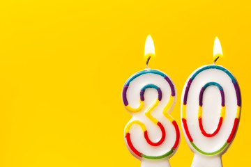 Number 30 birthday celebration candle against a bright yellow background
