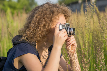 The girl with vintage camera is standing in the tall grass
