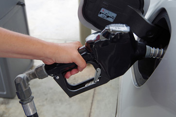 Hand holding Gas pump inserted into gas tank of a car