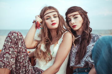 Portrait of Stylish hippie girls having fun at the sea side. Boho casual style.