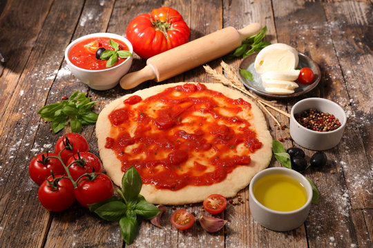 cooking pizza with tomato sauce,mozzarella and basil