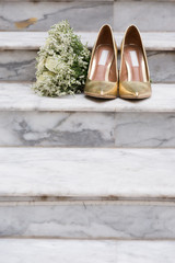 White Rose Bouquet and Gold Wedding Shoes on Marble Steps