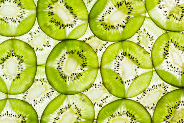 Close-up of green slice of kiwi fruit on a white background.