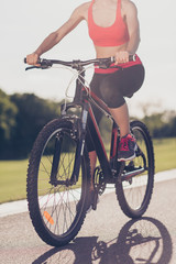 Cropped low angle photo of female athlete, cycling the modern bike on the track outdoors, in trandy outfit, sneakers