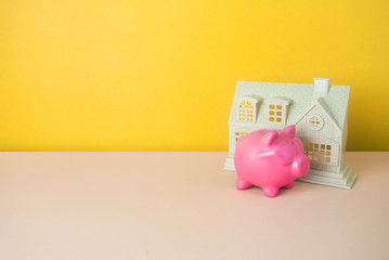 home and piggy bank in money finance concept