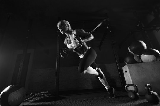 Fitness woman workout on the TRX in the gym