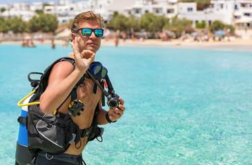 Taucher signalisiert das OK Zeichen vor türkisem Wasser der Ägäis, Griechenland