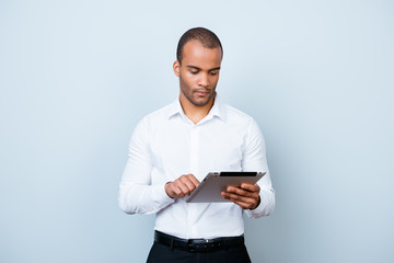Successful ponder young african guy is browsing at his tablet, standing on the pure background, being pensive and severe